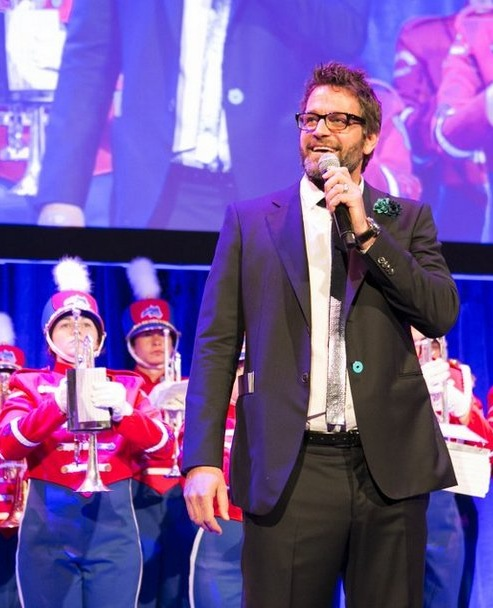 Peter Hermann, the evening's host, stands in front of the Spirit of Stony Brook Marching Band. Photography by: Michael Webber